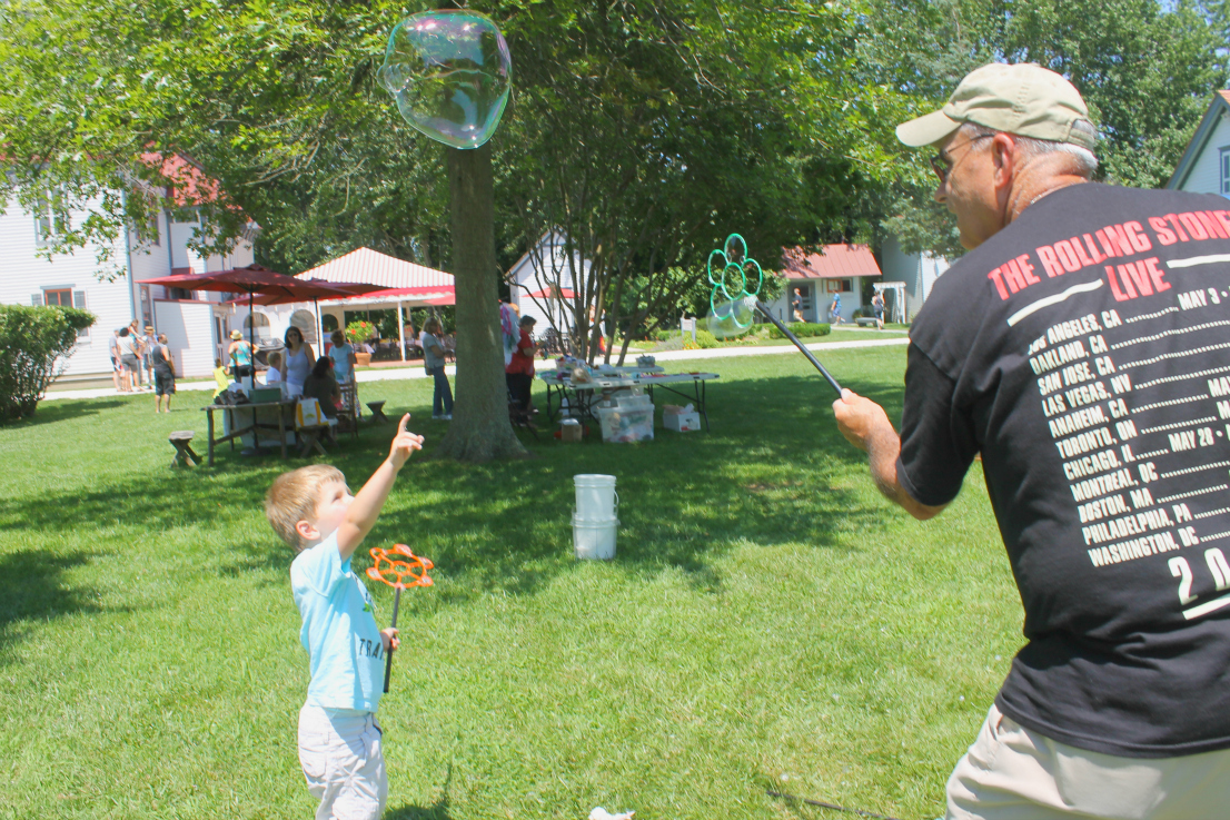 Father blowing bubbles with his kid