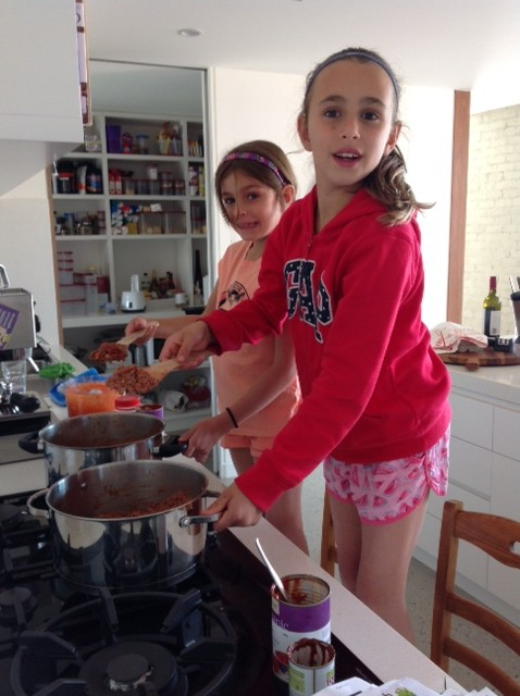 Kids cooking spaghetti Bolognese