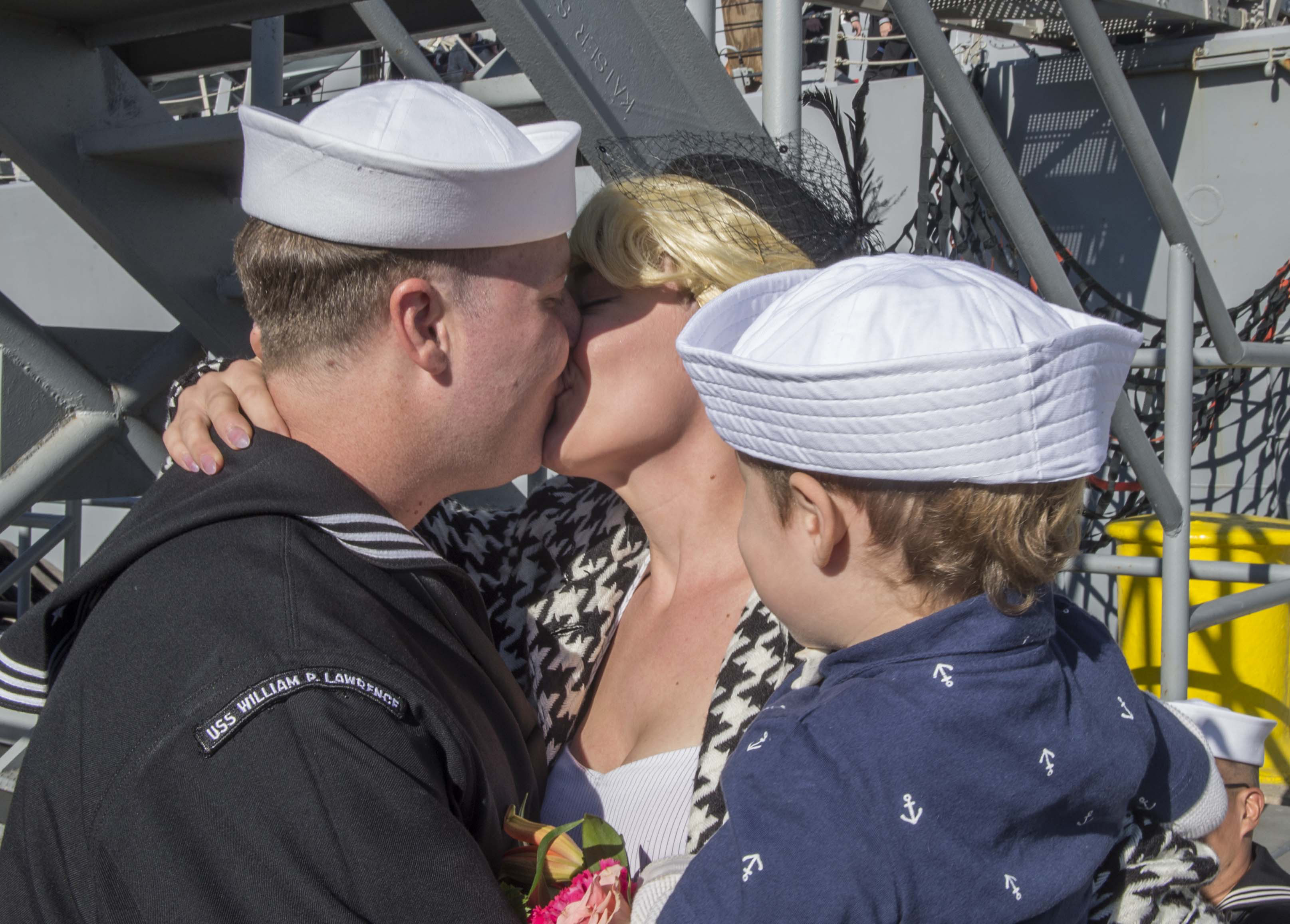 A sailor kissing his wife in front of son