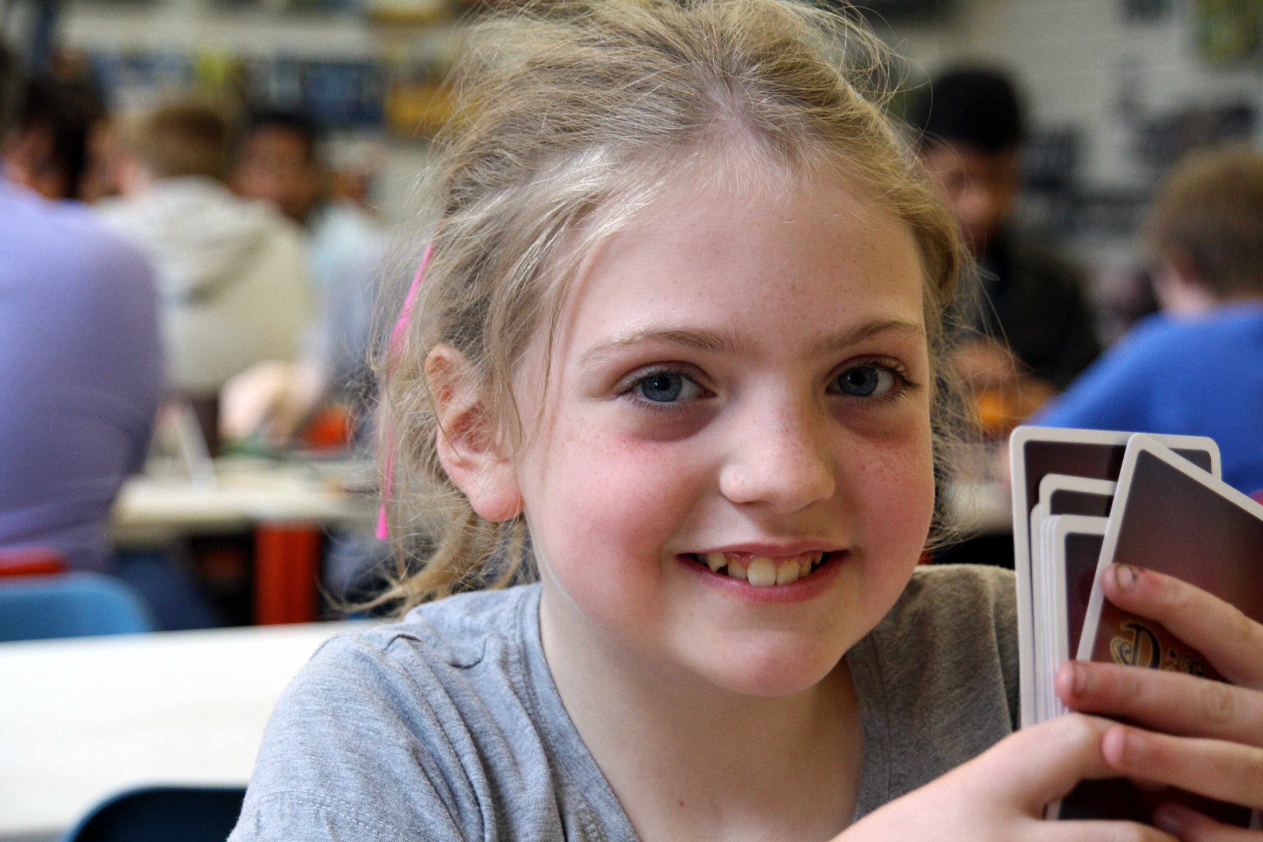 Little girl playing a card game and smiling to camera