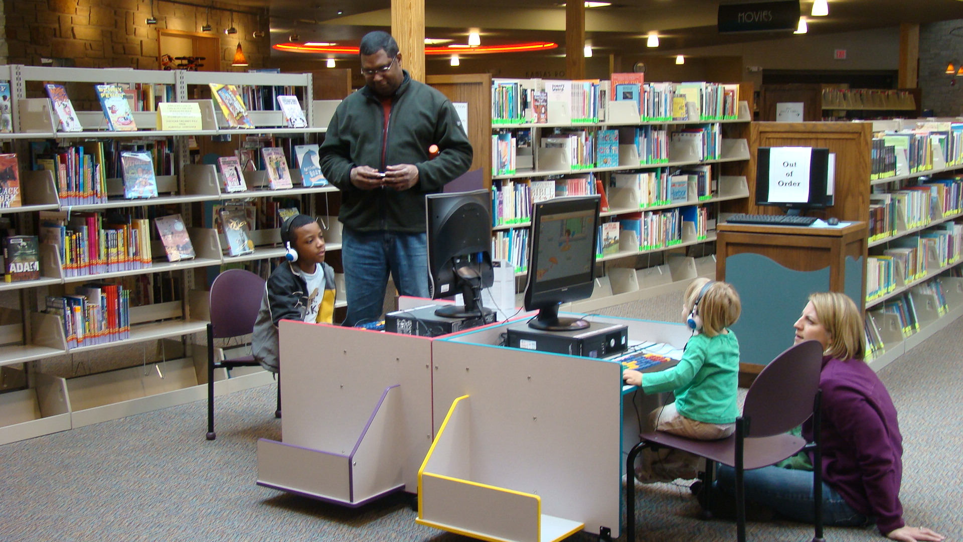 Dad spending time with kid at the community library's computer