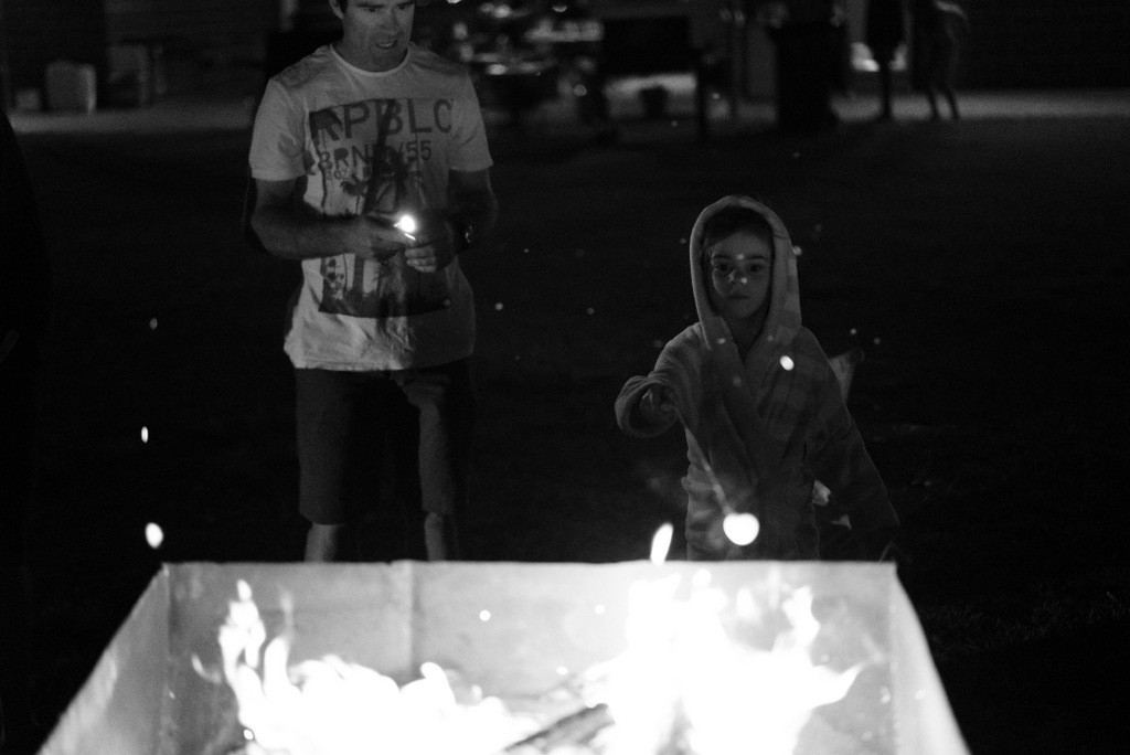 A child and dad roasting marshmallow