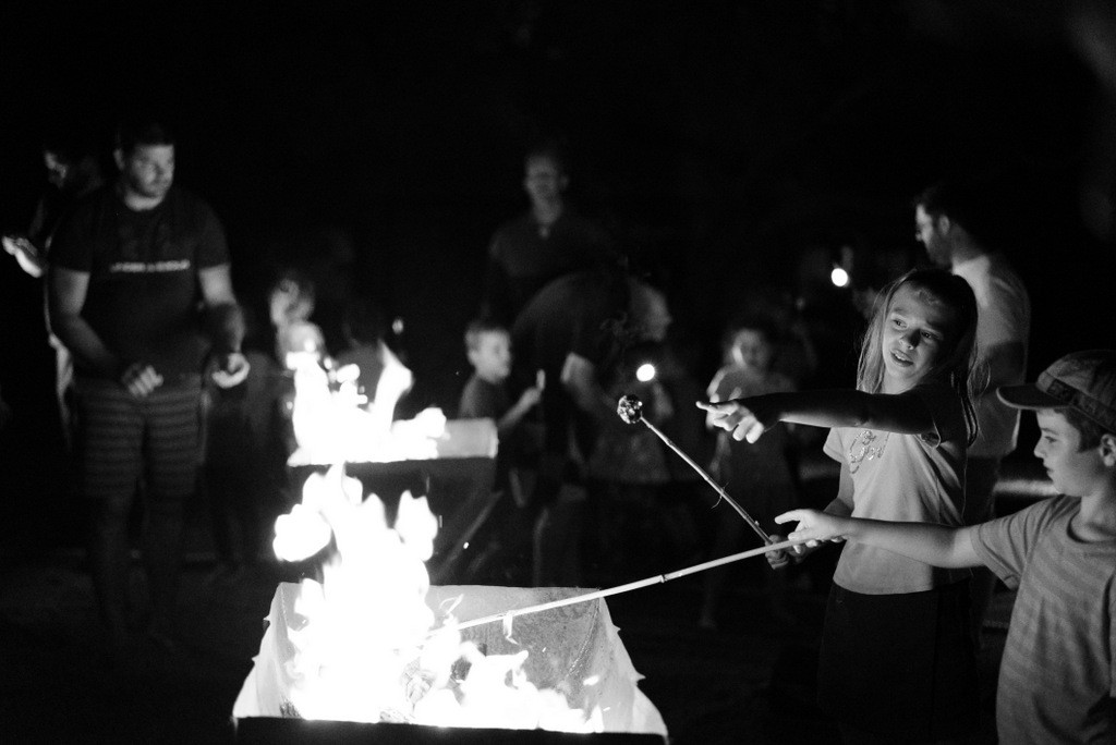 Young girl pointing at a marshmallow being roasted