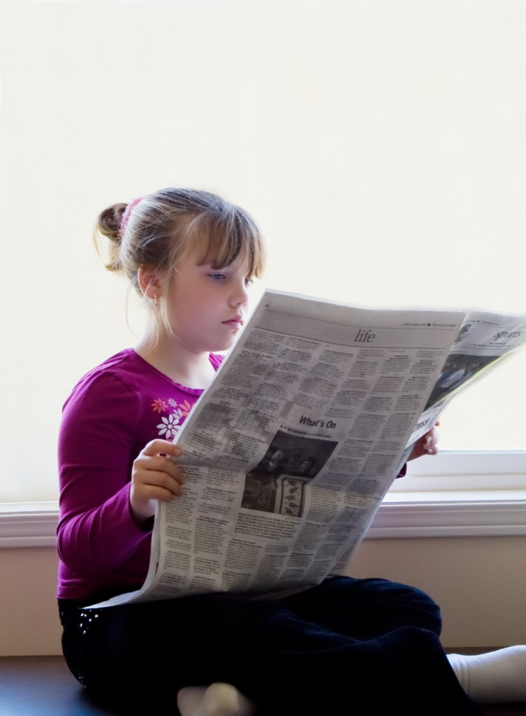 Current events: Young child reading a newspaper